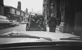 Bill Wyman bundled out of the back of a van, by stage door, Manchester 1964